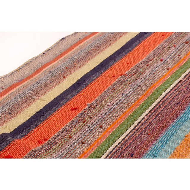 This contemporary kilim is joyful and inviting in a rainbow of colors and fun stripe pattern. A splendid assortment of...