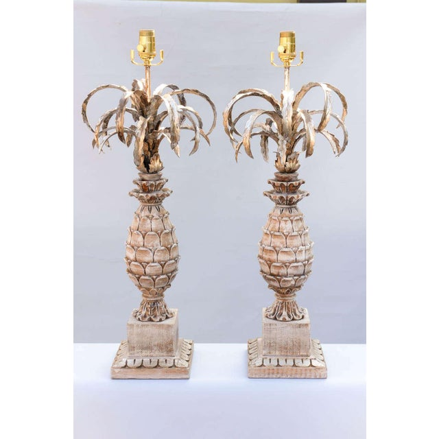 Pair of pineapple lamps, each having silvergilt iron leaves above a carved pickled wood pineapple, raised on square wood...