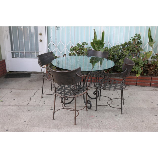Vintage set of wrought iron table with glass top in good condition. Chairs are all sturdy and well kept. No damages or...