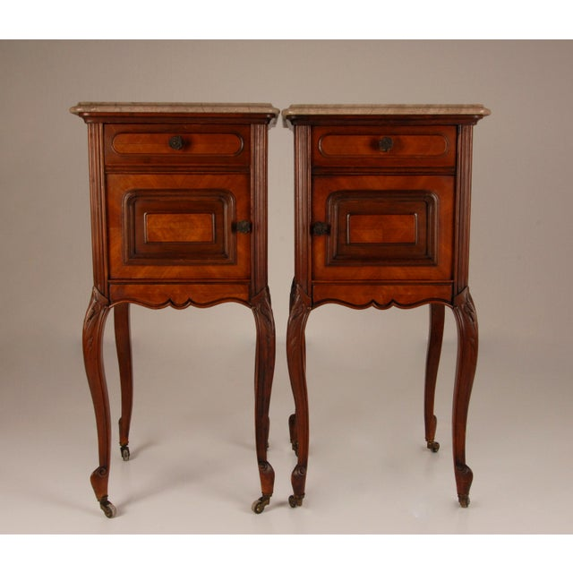 A pair French victorian nightstands on messing castors. Made rosewood verneer with a marble top. Hand carved mahagony and...