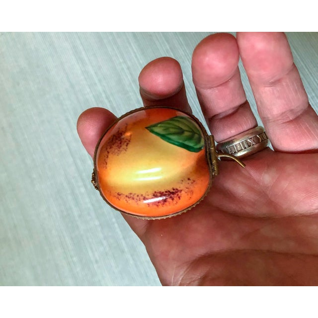 Gorgeous hand painted French porcelain box by Limoge in the shape of a peach fruit with a brass bee closure.