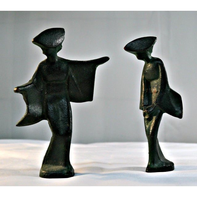 Graceful movement and simplicity in form are the main feature of this pair of mid-century, cast iron, geisha figurines...