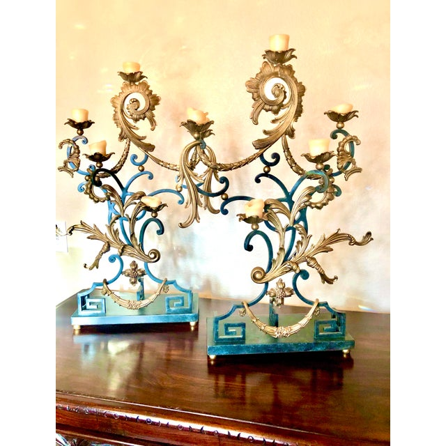 A pair of iron and brass five light candelabra/candleholder, the scrollwork arms adorned with brass leaves, swags and...