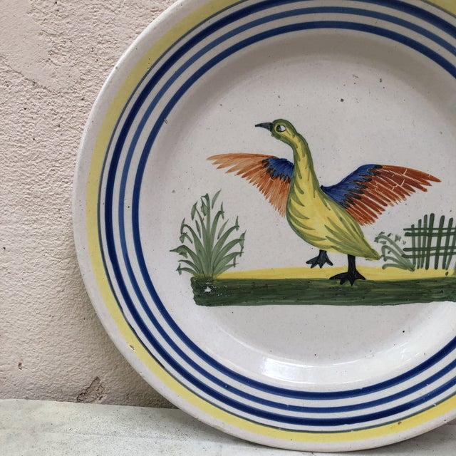 A French large faience plate with a bird signed Henriot Quimper, circa 1950. Colorful yellow border and blue lines....