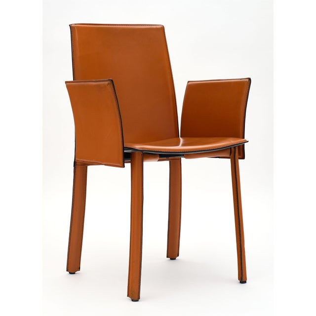 Vintage modernist orange leather armchairs from Italy. This pair is in excellent vintage condition and fully covered in...
