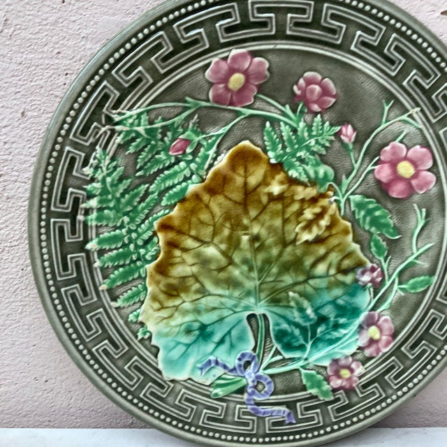 Majolica plate signed Choisy le roi, circa 1890. Decorated with leaves, ferns, pink flowers and Greek border.