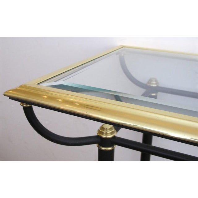 A good quality French 1960s brass and black console table with beveled glass top and lower shelf; the long inset glass top...