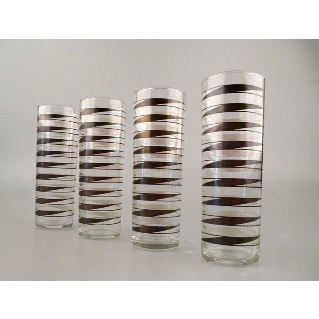 Set of four tall drink glasses by Libbey Glass. One glass has the brand mark logo on underside.