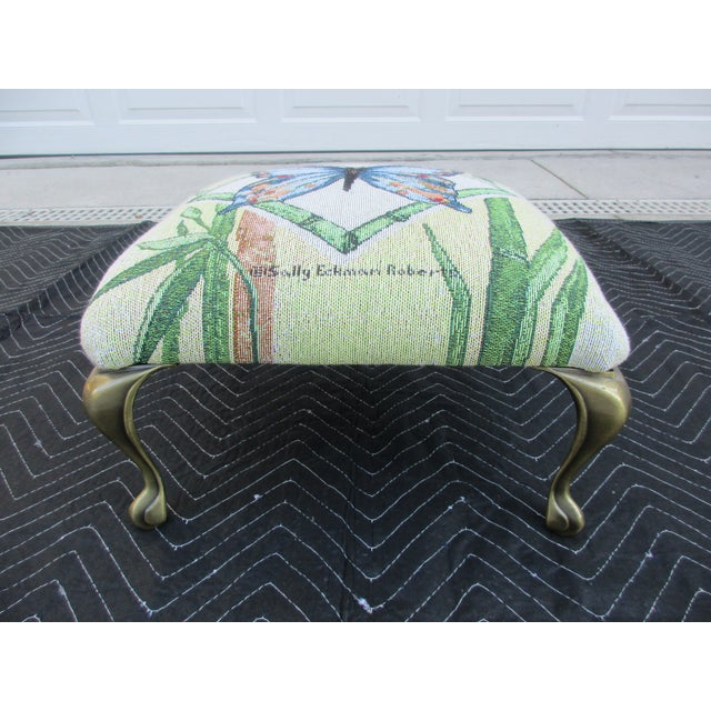 This beautiful footstool is covered by a Sally Eckman Roberts butterfly print fabric. The stool has brass cabriole legs...