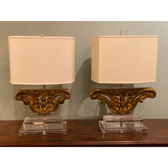 """A pair of antique gilt wood fragments mounted on lucite and repurposed as custom lamps. 25"""" High x 12"""" Wide x 6"""" Deep..."""