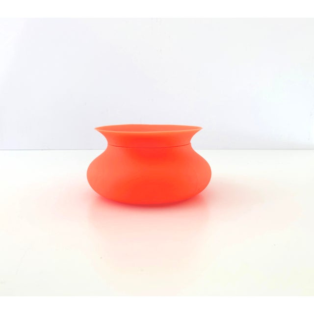 A cheerful, bright orange flexible silicone bowl with lid from Finell; perfect for storing little items around the house....