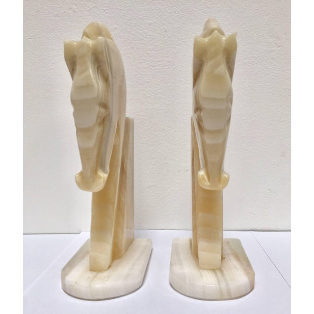 Pair of Art Deco style stylized horses head bookends. Vintage set of bookends, hand-carved in onyx in a shade of ivory and...