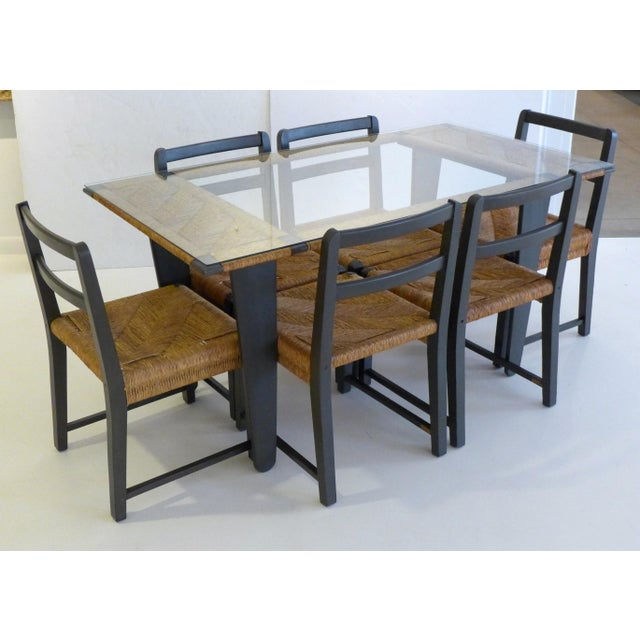 Dining table with six chairs, of painted pine with woven fiber cord. The table top features an open central section...