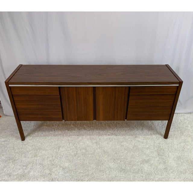 Handsome vintage mid-century modern walnut and credenza with chrome accent made by Kimball Furniture in the 1950s. Two...