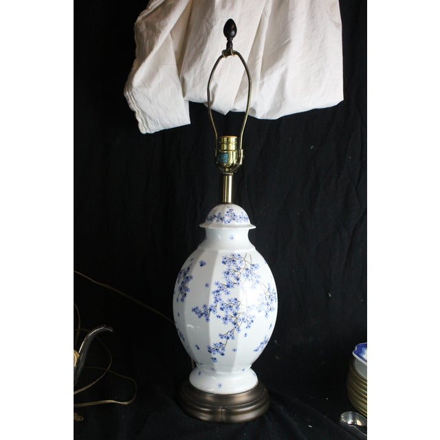 White Chinese porcelain table lamp with delicate blue hand painted design. Resting upon brass base.