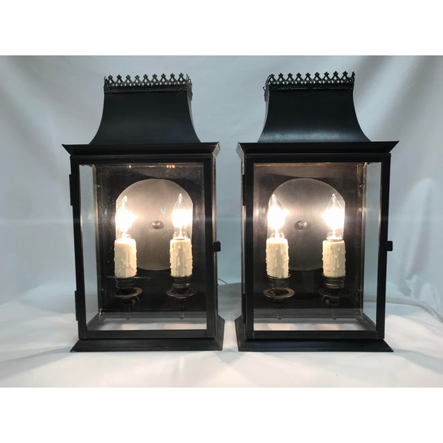 Restored pair of 1960s tole lanterns have been rewired, new sleeve covers. Original black finish over brass. Hinged glass...