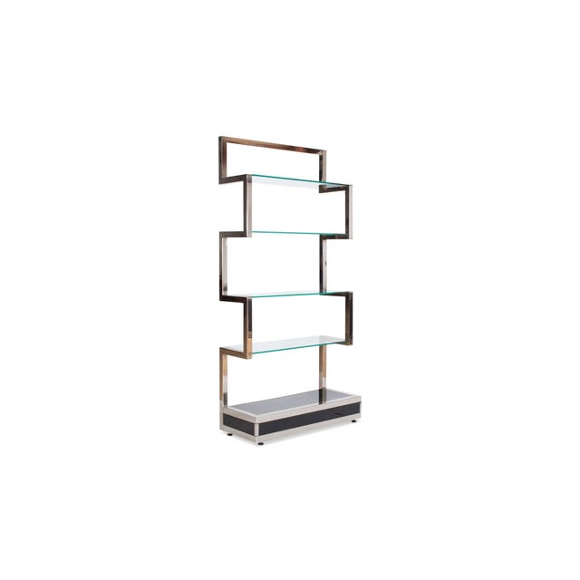 Chromed étagère by Belgo Chrome with clear glass shelving A black lacquered base with geometrical sides in chrome Highly...