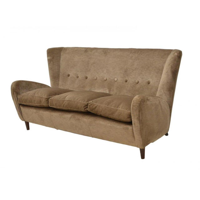 Italian Mid-Century Modern wingback sofa, designed by Paolo Buffa, circa 1950. The button back is accented with vertical...