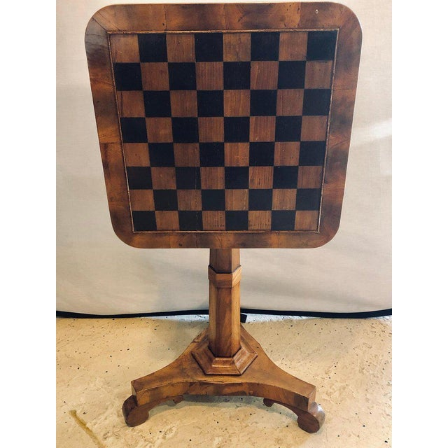 A 19th Century English Tilt Top Game Checkerboard or Card Table. This single pedestal flip top game table sits on a tri...