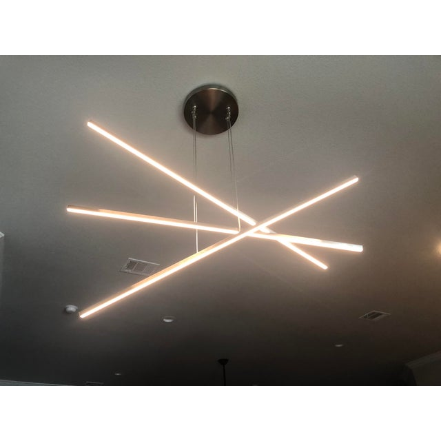 **Brand-new, unopened in box!** The ultimate in modern minimalism, this chandelier has 3 streamlined linear lengths which...