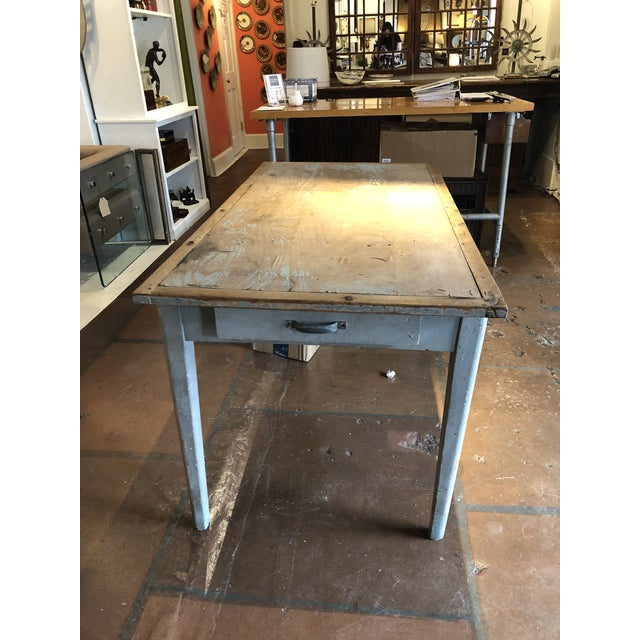 Antique continental two-drawer table with with paint and patina from outdoor use. This rustic work table is most likely...