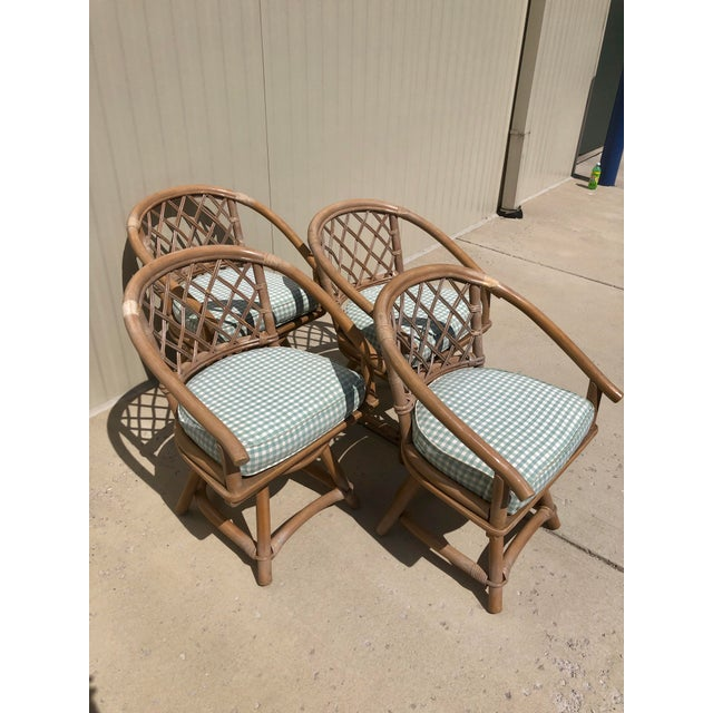 Classic set of four Ficks Reed swivel chairs with original natural rattan finish. The rounded backs have a criss cross...