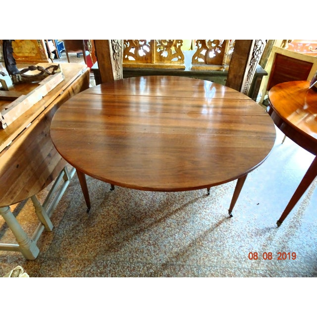 French 18th Century walnut dining room table. Epoch Directoire. 6 round tapered legs on wheels. Solid walnut. 2 leaves (...