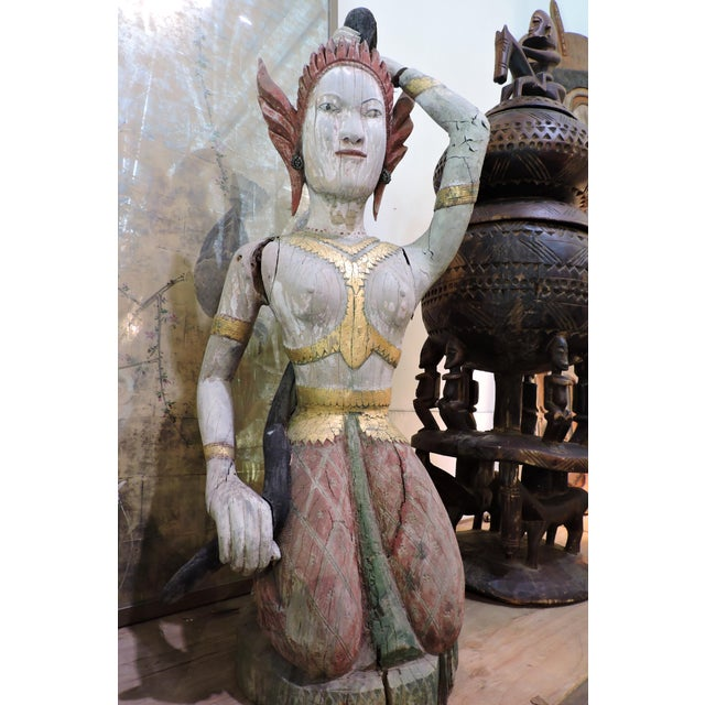 A well weathered carved and painted wooden statue of Phra Mae Therani, the Thai Earth Mother goddess wringing the cool...