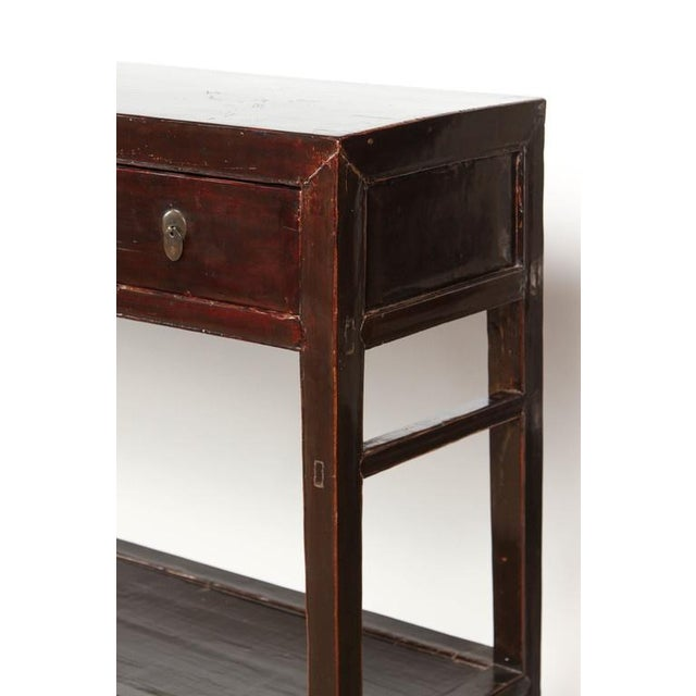 This 18th Century five-drawer black lacquer Chinese Shanshi table has egg-shaped pulls on each drawer in a matte gold...