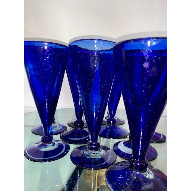 Set of 10 cobalt blue shrub glasses with unique swirls on the bases. Appear to be hand blown as each shape and swirl...