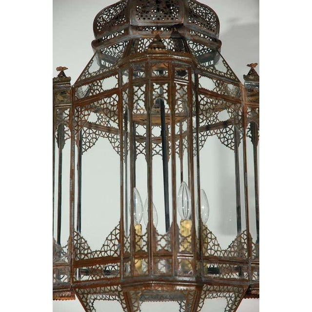 Very nice vintage handcrafted clear glass Moroccan lantern with intricate Moorish filigree designs on bronze finish metal....
