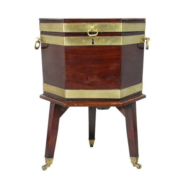 Hexagonal hinged top opening to a lead lined interior, conforming base with brass strapping and side handles, square...