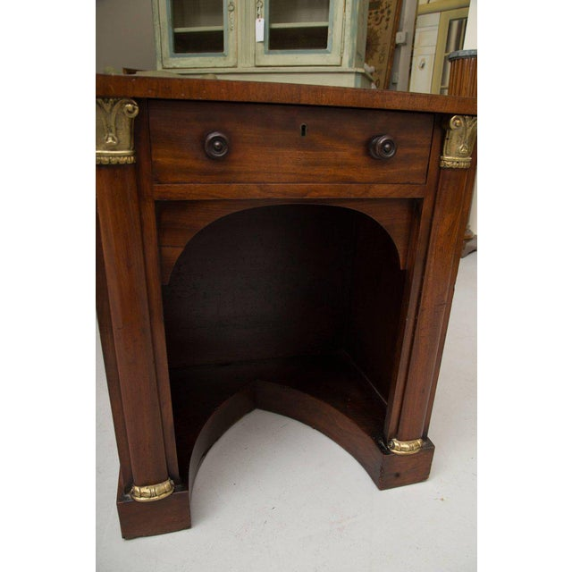 This is an unusual English Regency mahogany knee hole desk, the top with leather inset, above a frieze drawer flanked by a...