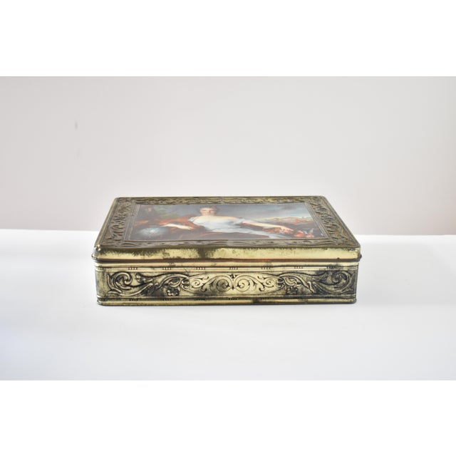 A vintage Italian biscuit tin by Pagani Lecco, featuring gilt scrolled sides and borders and the a lithograph reproduction...