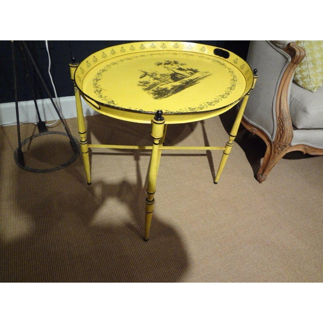 Charming Italian tole tray on stand in a great yellow color with a Neoclassical design from the 1940's. This versatile...