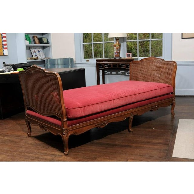 19th Century French Provençal daybed of cane and walnut in the style of Louis XV. The custom red velvet cushion rests on a...