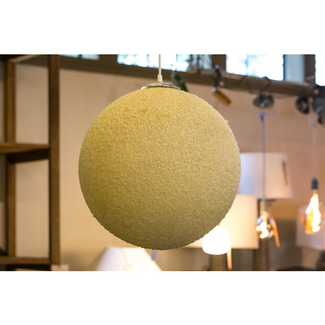 Modern textured globe-shaped light fabricated in plastic resin. This fun light might be interesting in a modern or coastal...