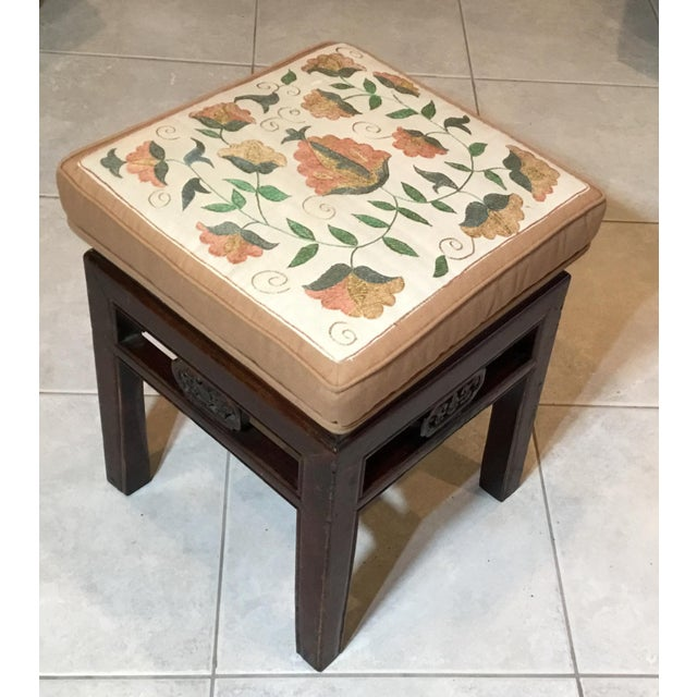 Antique Chinese sitting stool made of hand carved wood upholstered with hand embroidery silk Suzani textile surrounded...