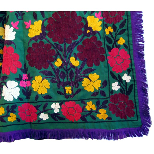 Gorgeous vintage embroidered Suzani has a dark green background of wool crepe with large burgundy and red flowers and...