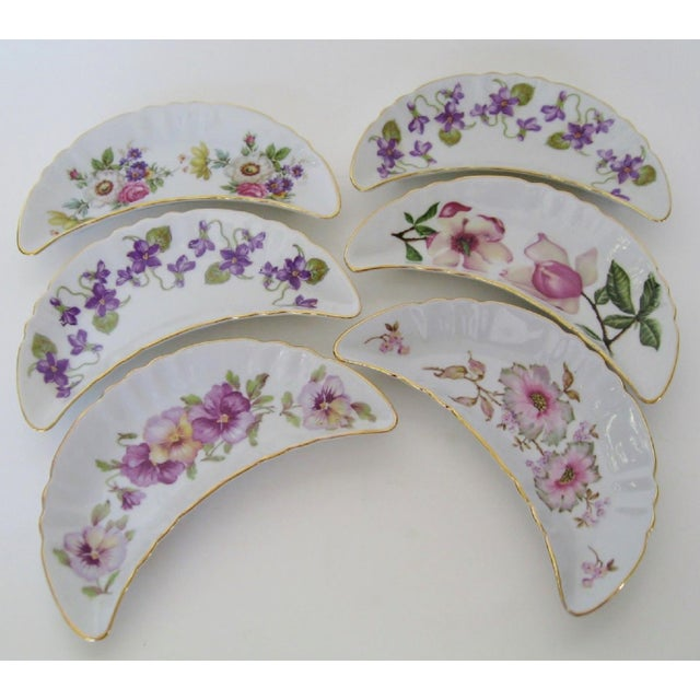 A collection of vintage Bavarian porcelain appetizer dishes in crescent shapes with hand-painted flowers that range from...