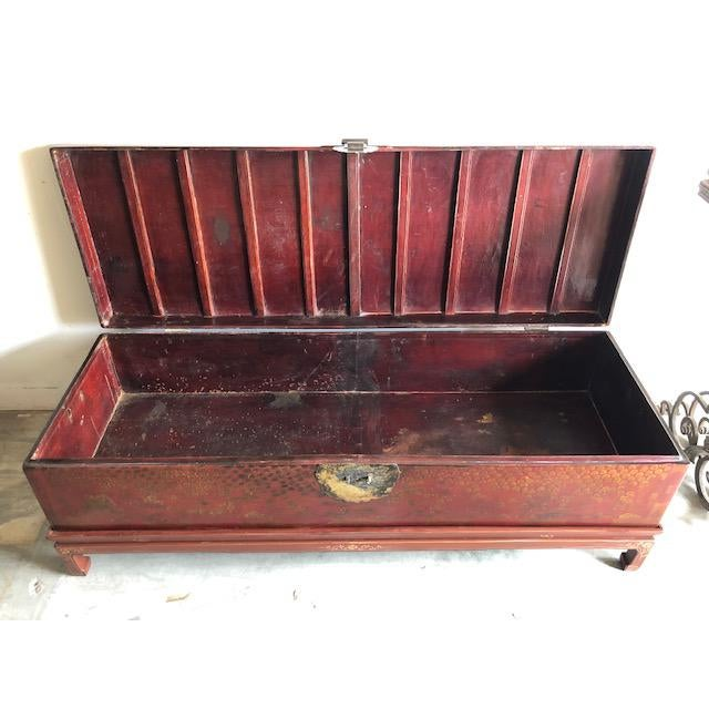 This is an antique Chinese martial arts storage chest that is red and gilt lacquered over leather. It has hand-painted...