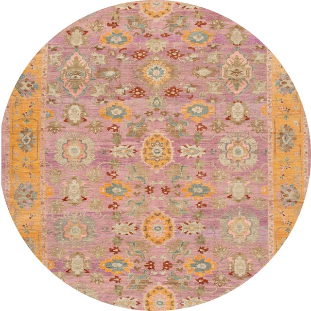 21st-century carpet with a light pink field, gold/orange, and cream design. This rug measures 12' 01'' x 15' 06'' .