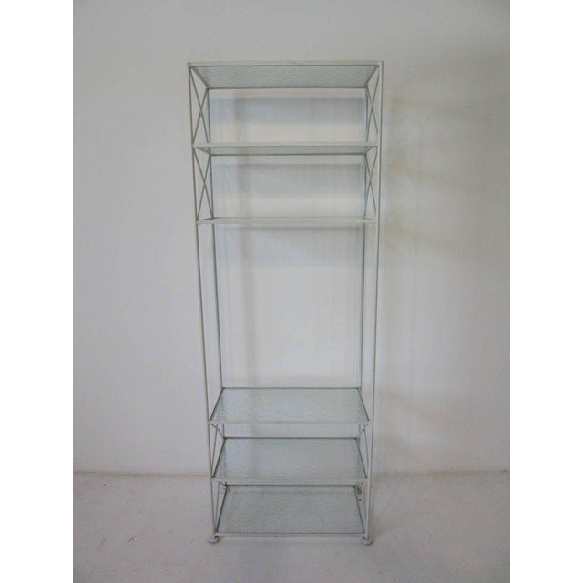 A hard to find satin white iron etagere or bookcase with pebbled glass shelves and X cross bracing manufactured by the...