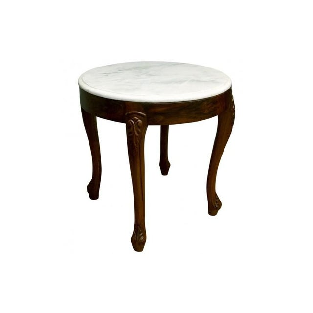 This understated accent table features carvings in a simple foliage design. It is topped with beveled white marble for a...