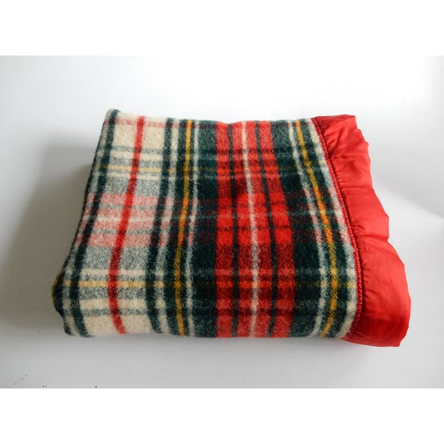 """A classic plaid wool blanket with red binding. Labeled """"Made by Pearce."""" Freshly cleaned and ready for use."""