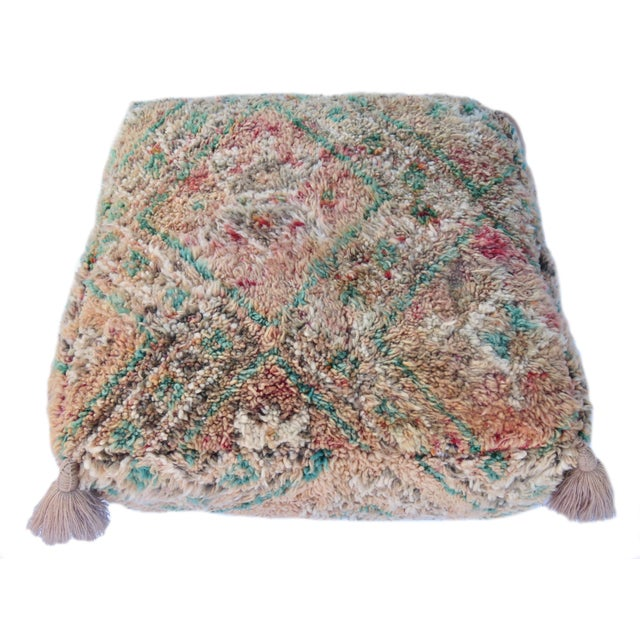 Moroccan floor pouf made from a vintage Berber rug handwoven with beige, taupe, ivory and green colored hand spun wool....