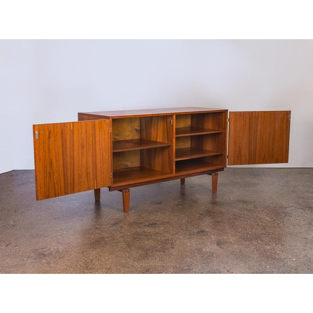 Elegant teak sideboard by Peter Lovig Nielsen. A beautiful example of 1960s Danish Modern cabinetry. The teak wood has...