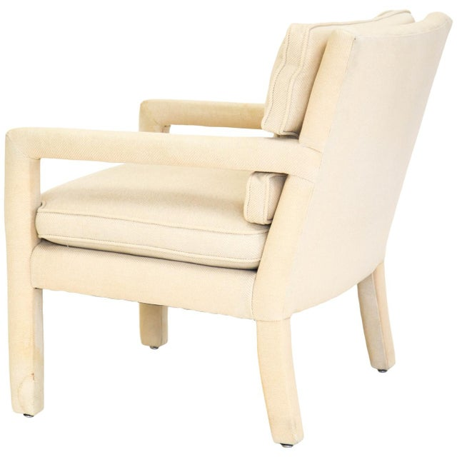 Mid-century upholstered lounge chair with thin right angle open arms in the style of Milo Baughman. With a loose seat...
