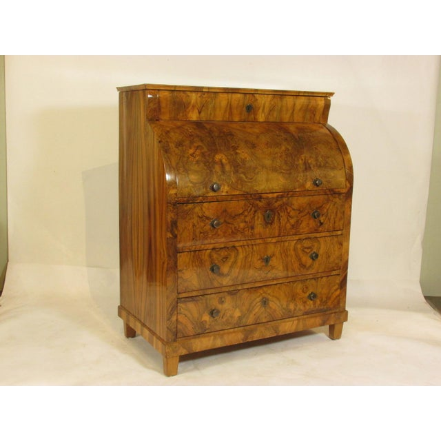 An exceptional early 19th-C. Biedermeier cylinder desk with book-matched fancy walnut veneered surfaces, a writing...