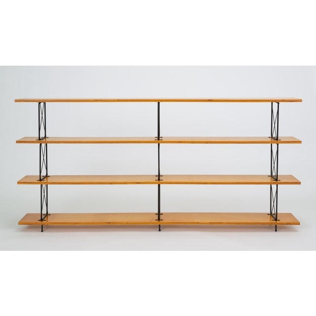 A versatile shelving or display unit with long mahogany plywood shelves and a framework in black-enameled steel. Each of...